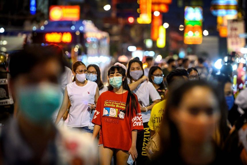 Pedestrians walk along a Bangkok street after coronavirus prevention measures are relaxed in May 2020.
