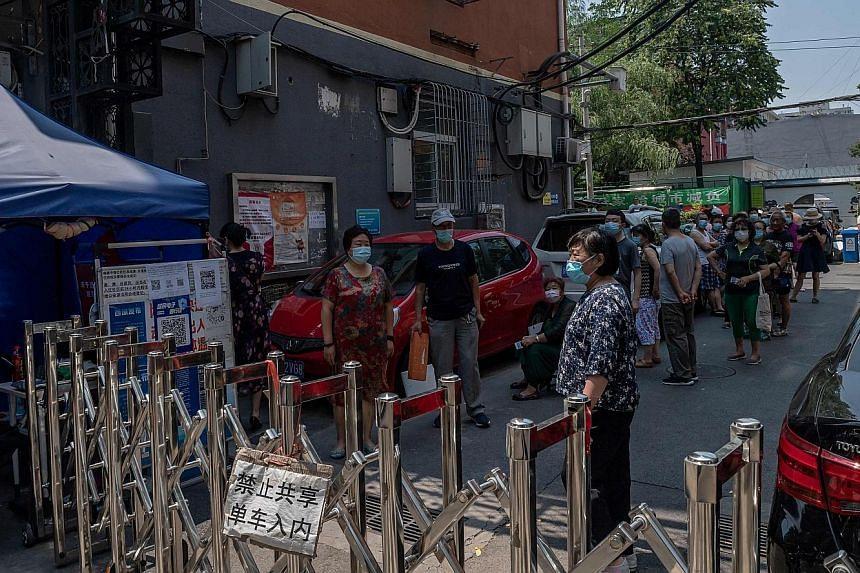 Residents under lockdown inside a compound in Beijing waiting to be taken to a site for Covid-19 testing yesterday. PHOTO: AGENCE FRANCE-PRESSE