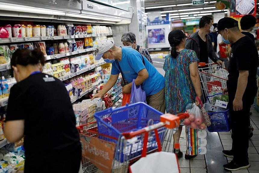 Customers inside a Beijing supermarket yesterday. Shops, restaurants and hair salons in many neighbourhoods in the city are still operating, despite the latest coronavirus outbreak linked to the Xinfadi market.
