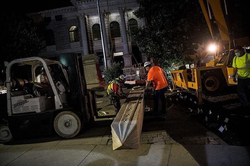 Members and supporters of Beacon Hill Black Alliance for Human Rights celebrating as workers removed the Confederate monument in Decatur, on the eve of Juneteenth. PHOTO: AGENCE FRANCE-PRESSE Workers removing a Confederate monument in Decatur, north-