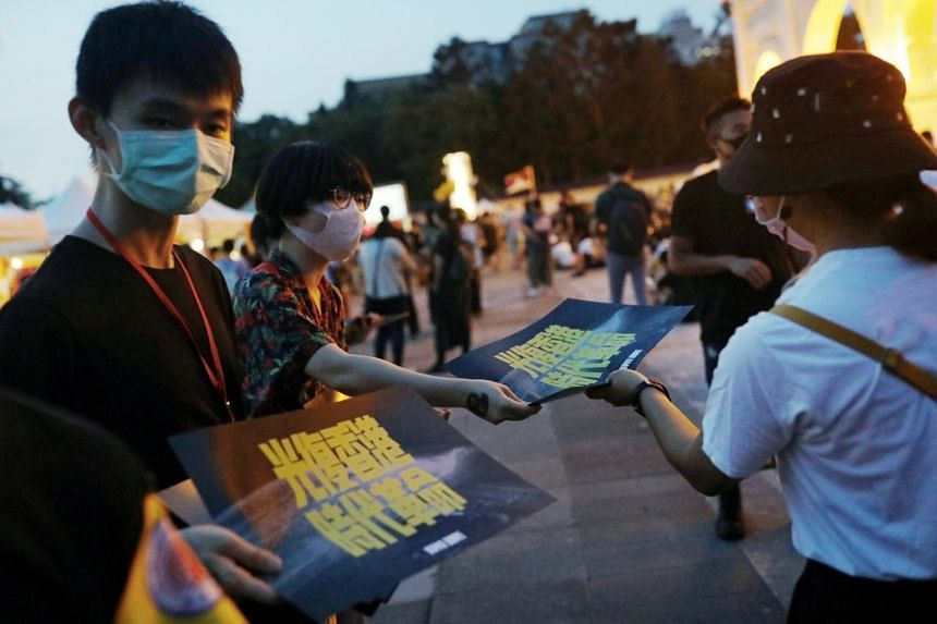 Volunteers hand out posters supporting Hong Kong anti-government movement in Taipei on June 13, 2020.