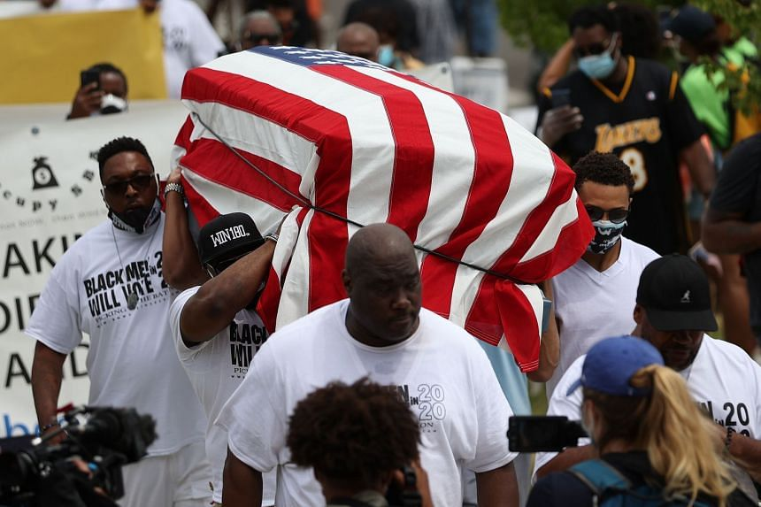 People carry an empty symbolic casket draped with the US flag during a Juneteenth march in Tulsa, Oklahoma.