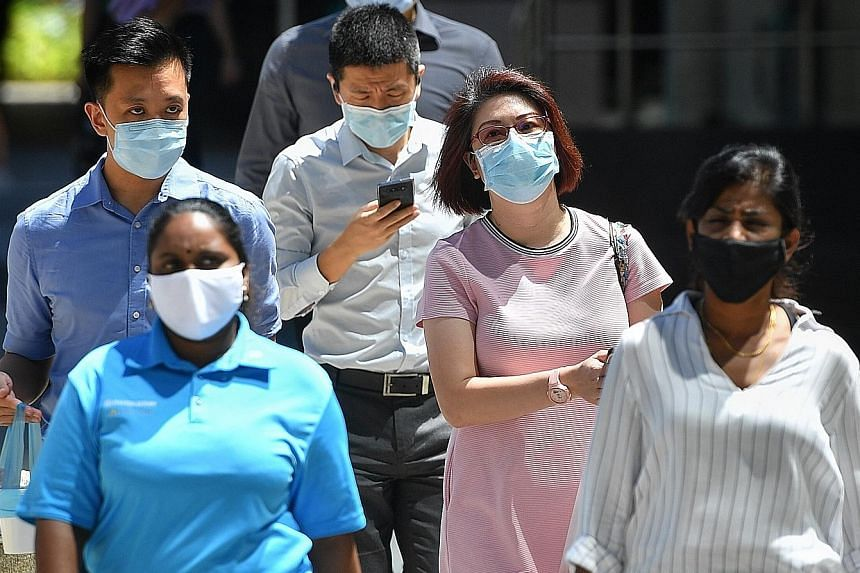 Residents at S11 Dormitory in April. Observers agree that the high numbers of infection among workers in dormitories could be an area of criticism on how the Covid-19 outbreak was handled by the Government. People waiting their turn to submit their a