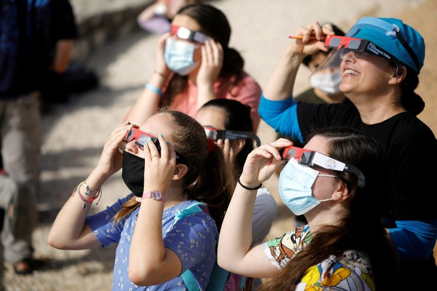People use protective glasses to observe a partial solar eclipse from Mount Scopus in Jerusalem on June 21, 2020.