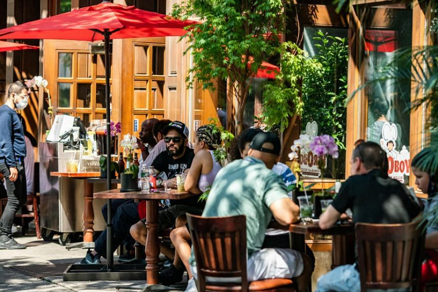 People eat in outdoor seating outside a restaurant in New York City, on June 21, 2020.