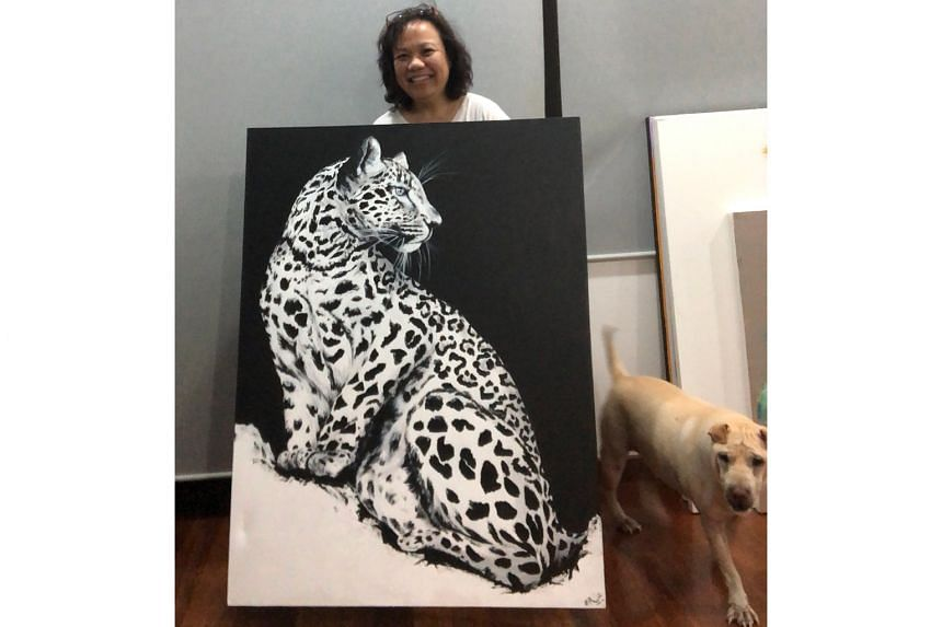 Artist Erica Wee with her painting of a leopard that represents a world on the lookout as the coronavirus was discovered. It is up for sale as part of the Sound of Art Covid-19 Fundraiser.