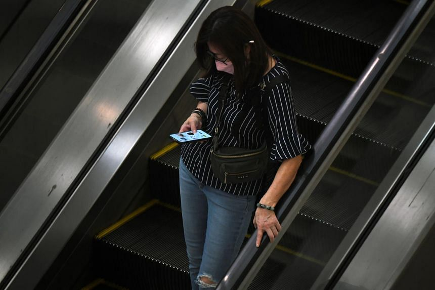 A commuter uses her mobile phone at the Dhoby Ghaut MRT station May 14, 2020.