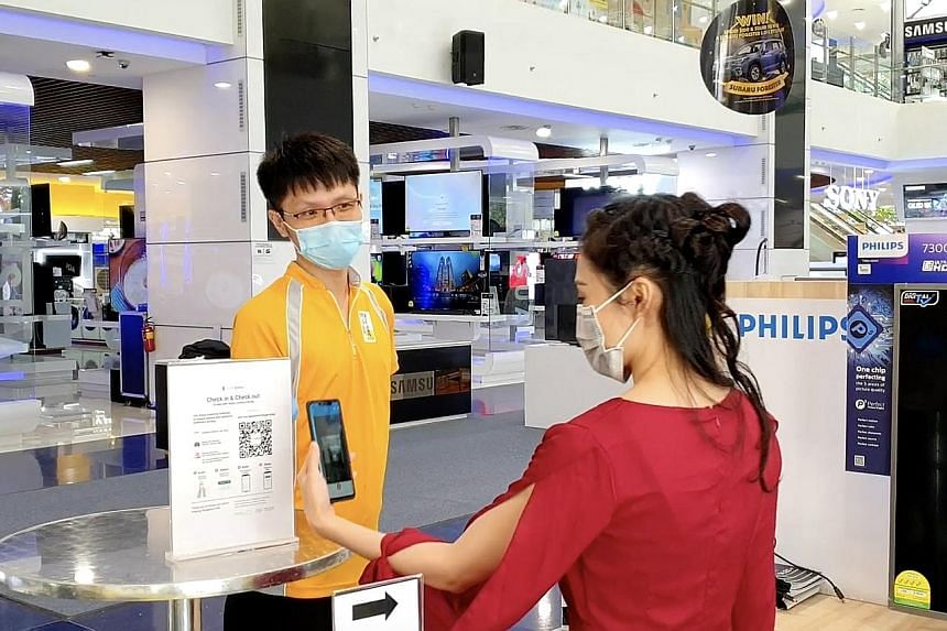 A shopper scanning a SafeEntry QR code at a Gain City store last Friday. Gain City said its stores saw a constant flow of traffic and good sales. Popular items purchased included washing machines, refrigerators, air-conditioning units and sofas. Peop