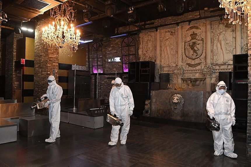 Quarantine workers disinfecting a night club in Itaewon in Seoul after crowds gathering over a holiday weekend in May sparked a fresh wave of coronavirus infections in the South Korean capital. PHOTO: REUTERS