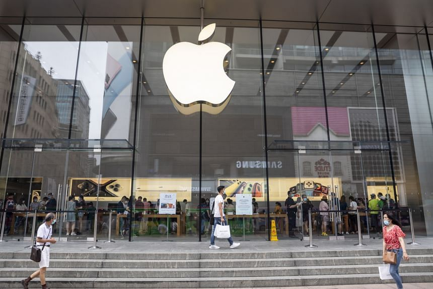 People pass in front of the Apple store in Shanghai on June 18, 2020.