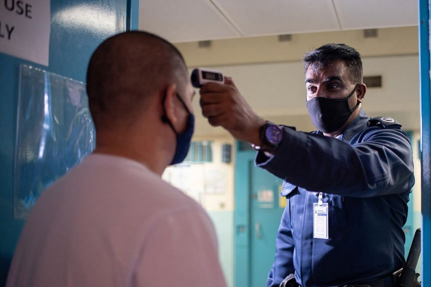 A prison officer checking an inmate's temperature in his cell. Some core rehabilitation programmes have resumed.