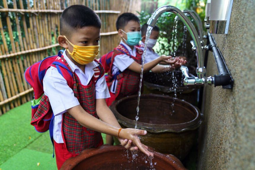 Kindergarten students wearing face masks cleaning their hands in Bangkok, on June 23, 2020.