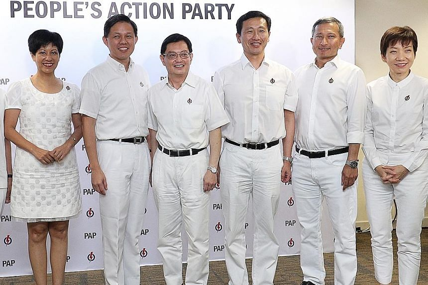 National Development Minister Lawrence Wong (second from left) and his Marsiling-Yew Tee GRC team - (from left) Mr Ong Teng Koon, Mr Zaqy Mohamad and Mr Alex Yam - are launching a series of live chats with residents on Facebook today, amid limits on