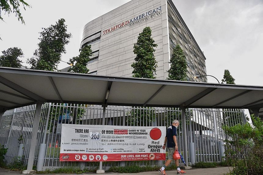 A red dengue alert banner outside the Stamford American International School in Woodleigh Lane on June 16. The Woodleigh area in Potong Pasir is the largest dengue cluster, with 212 infections.