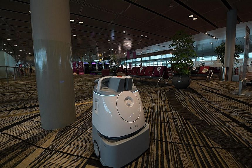 A robot vacuum cleaner doing its job in the transit holding area at Changi Airport's Terminal 3 yesterday. (From left) Changi Airport Group (CAG) chief executive Lee Seow Hiang, Transport Minister Khaw Boon Wan, CAG senior vice-president for passenge