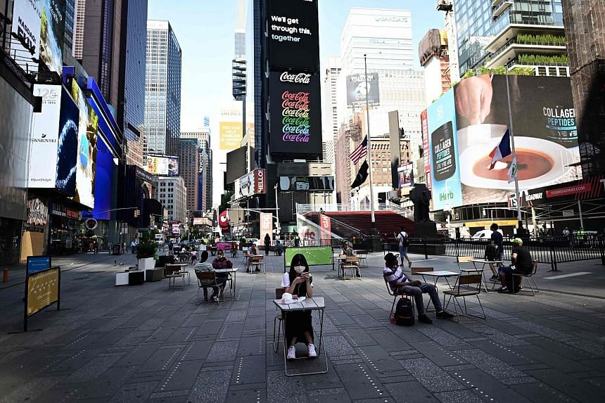 Times Square in New York City on Monday. The metropolitan area was the last region to move into phase two of New York state's economic reopening plan. PHOTO: AGENCE FRANCE-PRESSE A busy barber shop and a Bloomingdale's department store in New York Ci