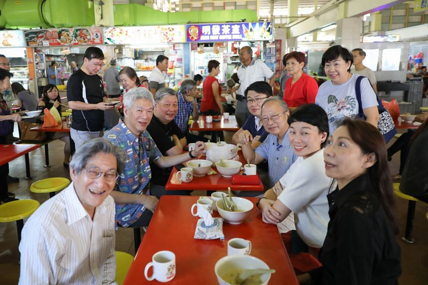A photo taken on Nov 4, 2018, showing Dr Tan (seated, third from right) and Mr Lee (second from left) at West Coast Market and Food Centre.