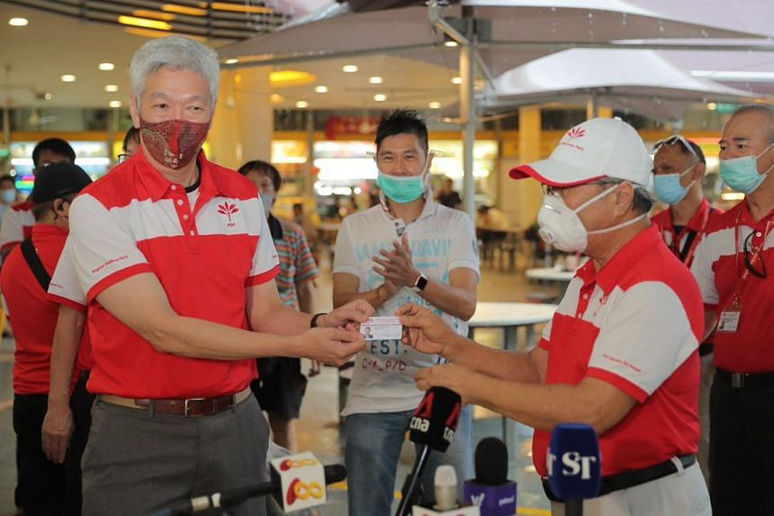 Mr Lee Hsien Yang (left) being presented with a Progress Singapore Party membership card by PSP chief Tan Cheng Bock at Tiong Bahru Market on June 24, 2020.