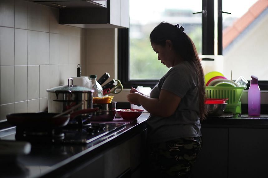 A foreign domestic helper prepares dinner in the kitchen on April 27, 2020.