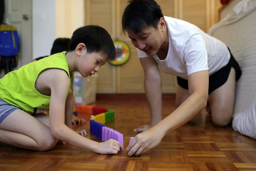 A boy and his father play with coloured blocks together on April 24, 2020.