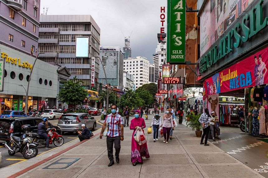 People walking along a shopping area in Kuala Lumpur on May 21, 2020.