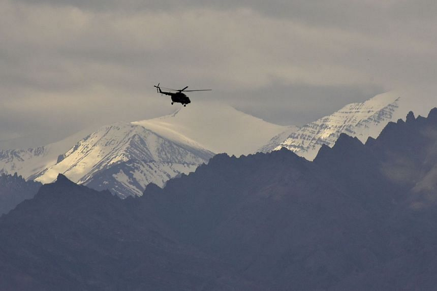 An Indian air force helicopter flies above mountains near Leh, Ladakh, June 24, 2020.