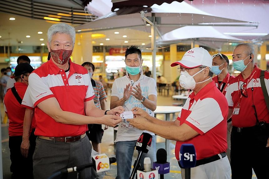 Progress Singapore Party secretary-general Tan Cheng Bock (right) presenting Mr Lee Hsien Yang with the membership card yesterday at a breakfast meeting at Tiong Bahru Market, which is located in Tanjong Pagar GRC. The constituency, which was a stron