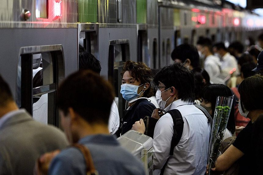 People boarding a train at Shinagawa station in Tokyo during the evening rush hour yesterday. The daily number of new Covid-19 cases in the Japanese capital climbed to 55 yesterday. Amid the spike in cases, traffic at major stations in the city has b