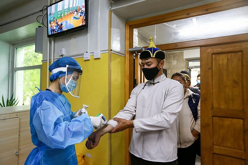 A man with a face mask has his temperature checked as he arrives to vote at a polling station in Ulaanbaatar, the capital of Mongolia. Medical staff were also present yesterday to hand out disinfectant and single-use plastic gloves to voters who were