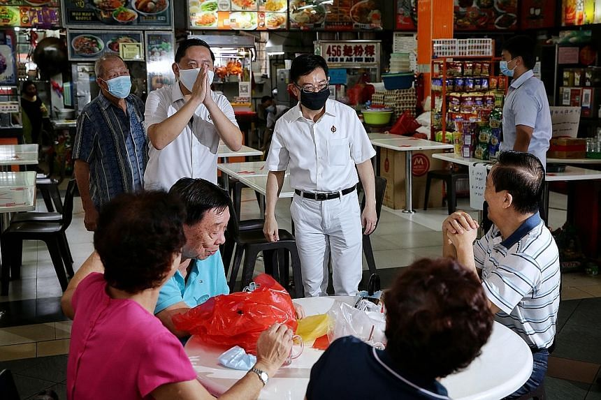 Singapore Democratic Party's likely candidates for Holland-Bukit Timah GRC, Mr Alfred Tan and Ms Min Cheong, at Ghim Moh Market on Sunday. PHOTO: MIN CHEONG/ FACEBOOK Deputy Prime Minister Heng Swee Keat (centre) meeting residents in New Upper Changi