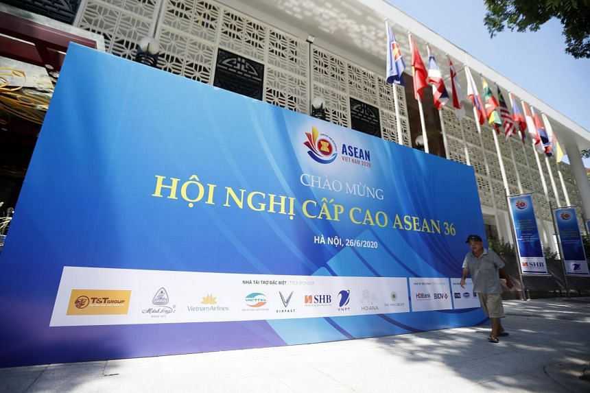 A man walks in front of a billboard promoting the upcoming 36th ASEAN summit in Hanoi on June 22, 2020.