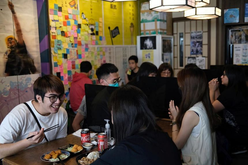 """In a photo from May 1, 2020, customers sit inside a """"yellow"""" restaurant with pro-democracy views in Hong Kong."""