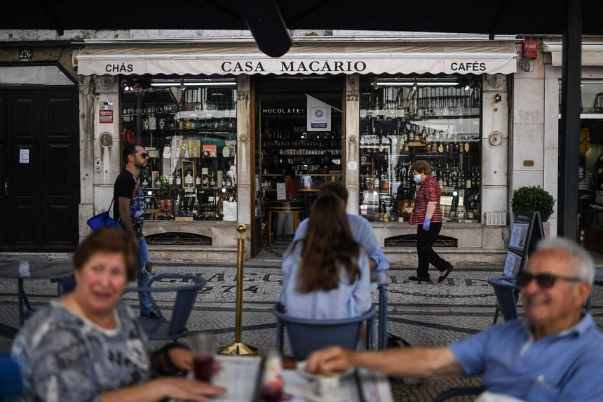 People sit at a terrace bar in downtown Lisbon on June 23, 2020.