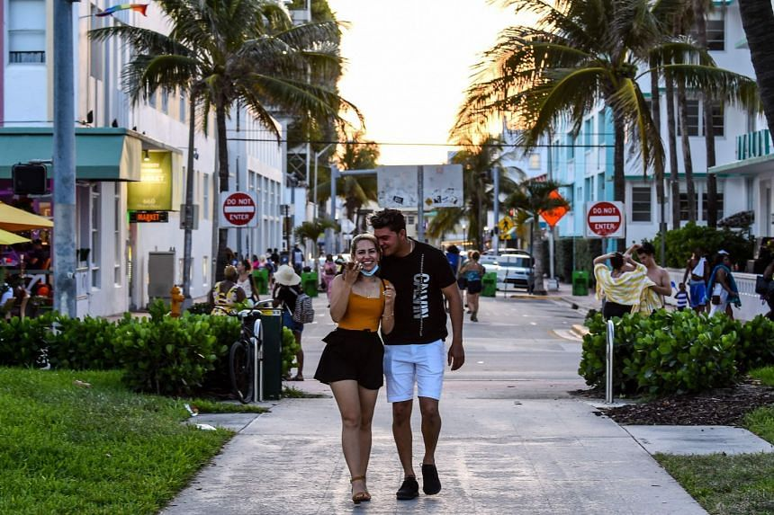 A couple embrace each other as they walk on Ocean Drive in Miami Beach Florida