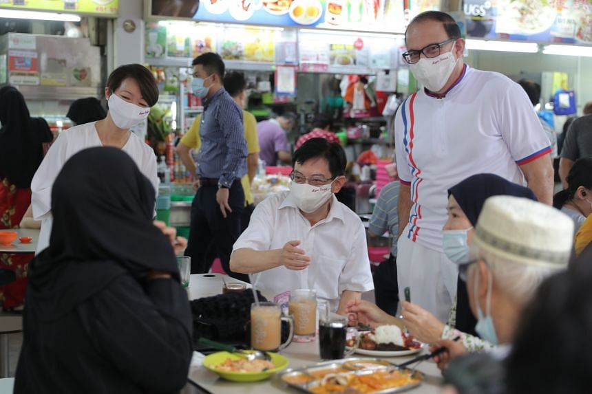 Deputy Prime Minister Heng Swee Keat (seated, in white) with PAP team members Foo Mee Har and Communications and Information Minister S. Iswaran at Teban Gardens Market and Food Centre in West Coast GRC on June 27, 2020.