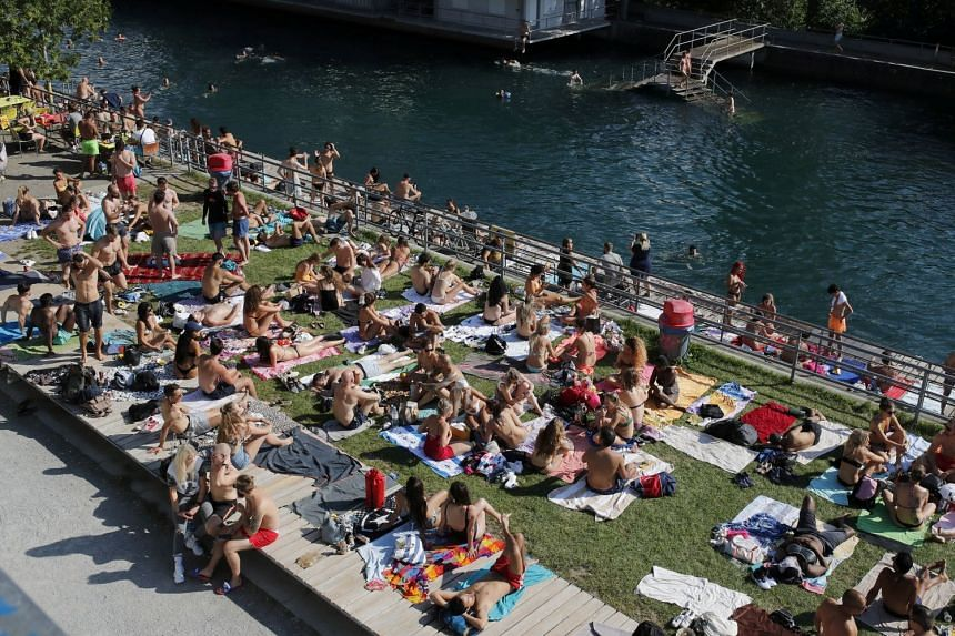People enjoy hot summer weather on the banks of the Limmat river in Zurich, June 27, 2020.