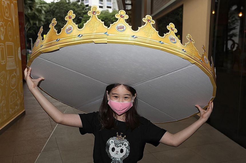 Nine-year-old Valerie Chew wears Burger King's social-distancing crown, which ensures that dining companions are kept a metre apart.