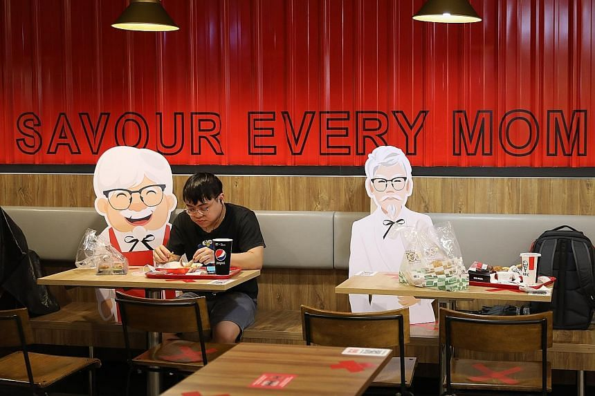 Colonel Sanders cut-outs sit among diners at the KFC outlet at Novena Square.
