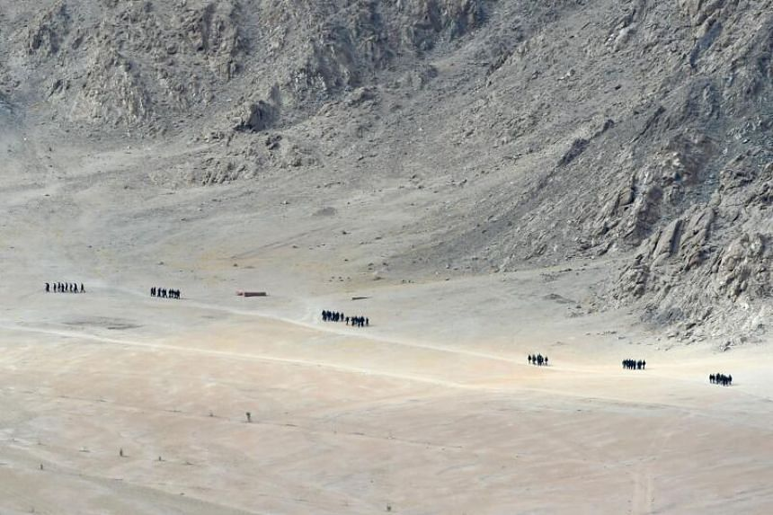 Indian soldiers walk at the foothills of a mountain range near Leh, Ladakh, on June 25, 2020.