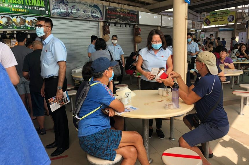 WP secretary-general Pritam Singh and chairman Sylvia Lim speaking with residents at Serangoon Garden Market & Food Centre on June 28, 2020.
