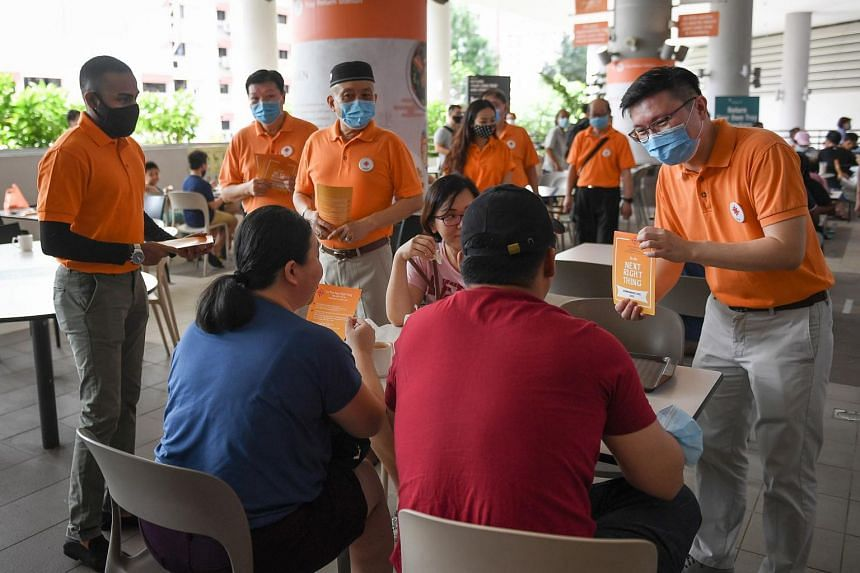 Mr Sathin Ravindran, 27 (far left) accompanies NSP secretary-general Spencer Ng as they speak to residents at Kampung Admiralty Hawker Center, on June 28, 2020.