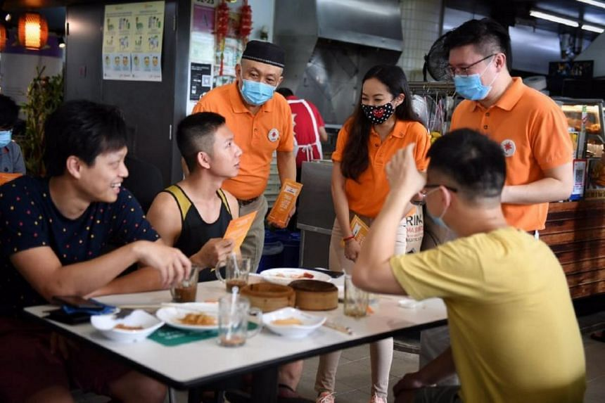 NSP members (standing, from left) Mr Yadzeth Hairis, Ms Kevryn Lim and Spencer Ng interacting with residents at Kampung Admiralty Hawker Center, on June 28, 2020.