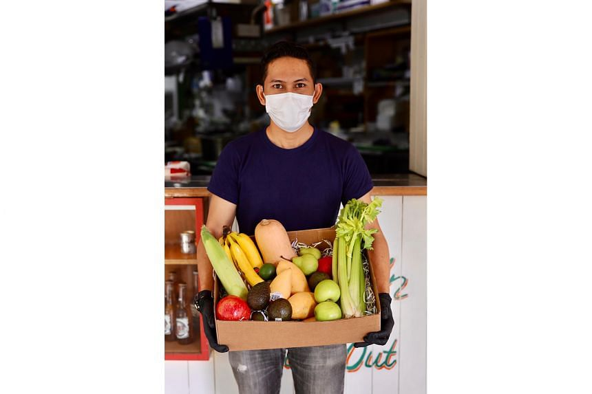 The Loco Group's floor manager Akhi Muhammad with a box of vegetables customers can buy direct from its chain of Mexican restaurants.