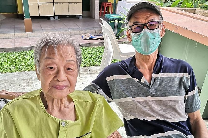 Madam Yap Lay Hong with her second son Alan Ho last Thursday at a designated outdoor area at Lee Ah Mooi Old Age Home, away from other residents.