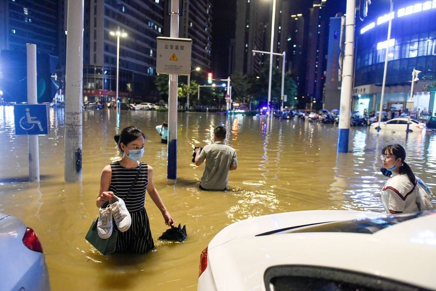 People wading in floodwater in Hefei, China, on June 27, 2020.