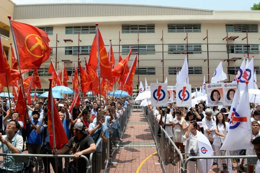 In a photo taken on Sept 1, 2015, Workers' Party and People's Action Party supporters gather at Fengshan Nomination Centre.