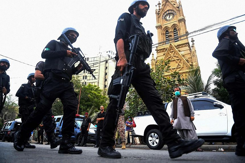 Police commandos patrolling near the Pakistan Stock Exchange in Karachi after an attack on the building by gunmen yesterday.