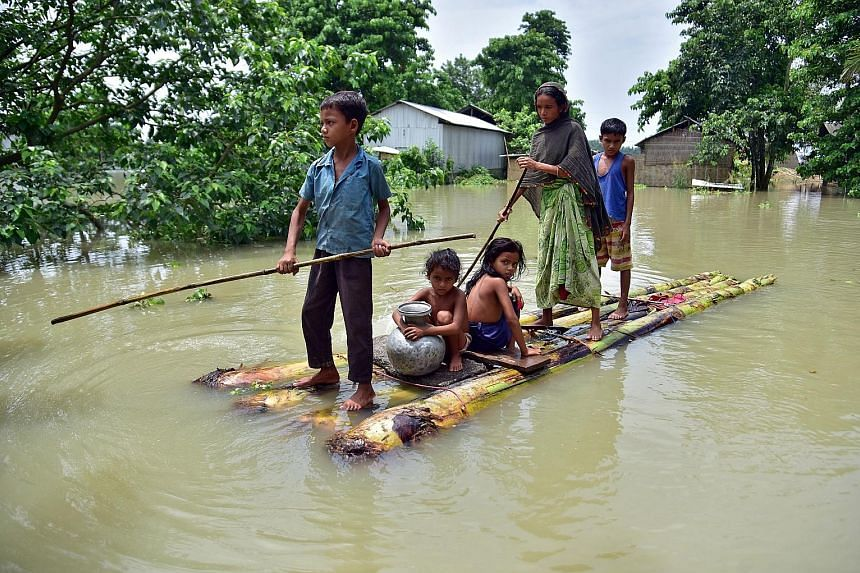 Villagers making their way on a makeshift raft through a flooded field to reach a safer place in the north-eastern Indian state of Assam yesterday. Torrential rain hit at least 23 of the state's 33 districts.