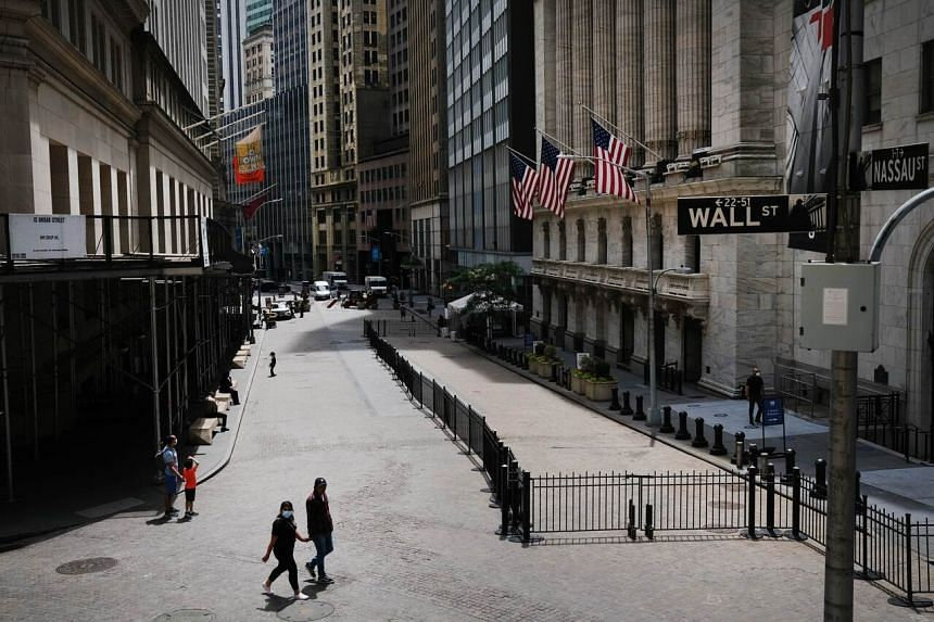 People walk by the New York Stock Exchange in an empty financial district on June 15, 2020.
