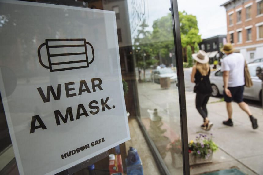 """People walk past a sign reading """"Wear a Mask"""" in Hudson, New York, on June 28, 2020."""